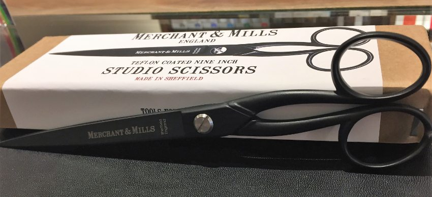 Image of Merchant and Mills studio scissors, with a pair of the scissors in the foreground and their package in the background.