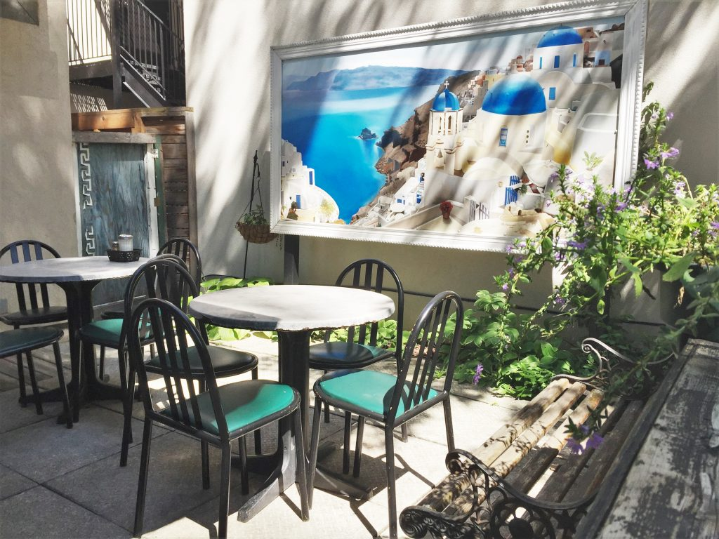 Photo of the Mural in the Scollard Deli Patio. The mural depicts a hillside town in Greece.
